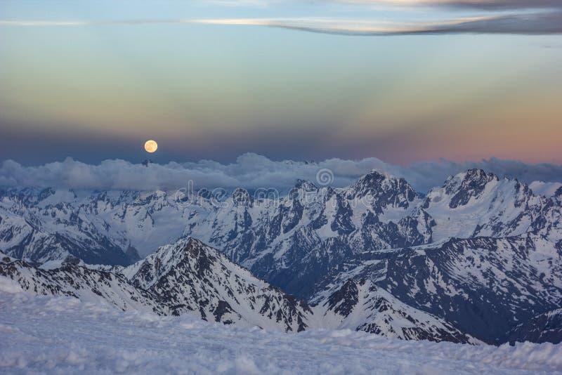 Snöig Kaukasus berg på solnedgången med moonrising och Anticrepuscular strålar royaltyfri foto