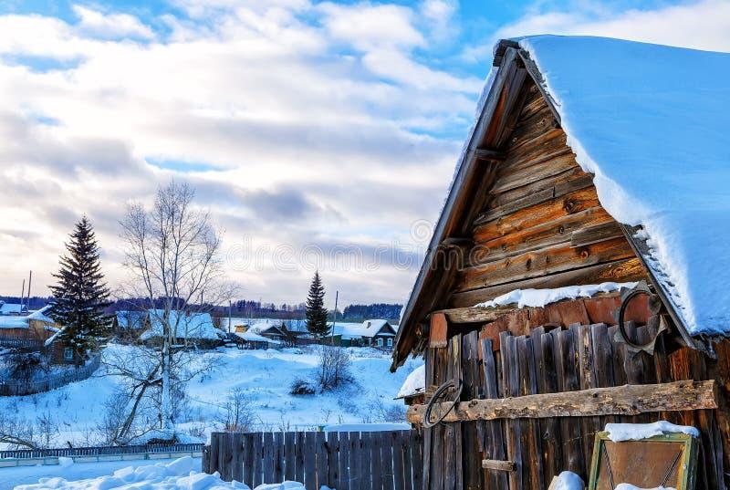 Snöig kullar i rysk bygd i morgon, röda trähusfönster vände till öst arkivfoto