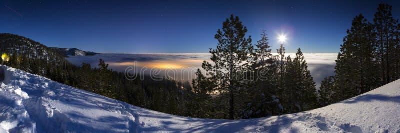 Snöig landskap för kall vinter på natten med ljus för stad för molninversion täckande som glöder under molnräkningen Lit med mu arkivfoto