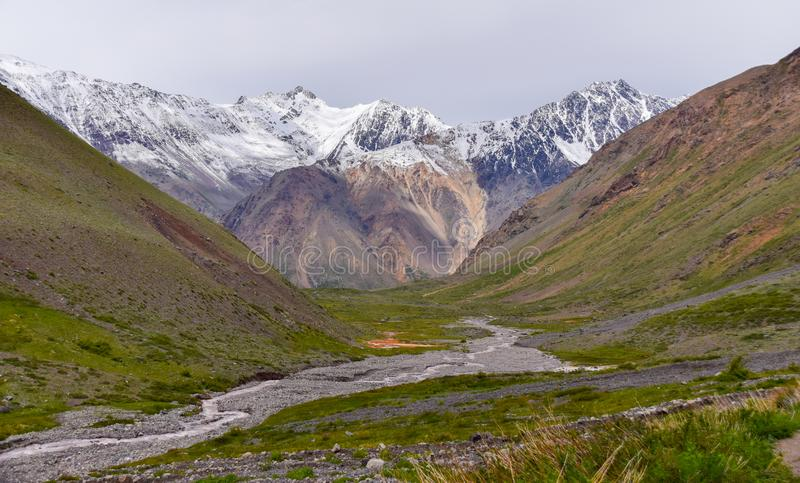 Snöig landskap med berg och en flod framme arkivbild