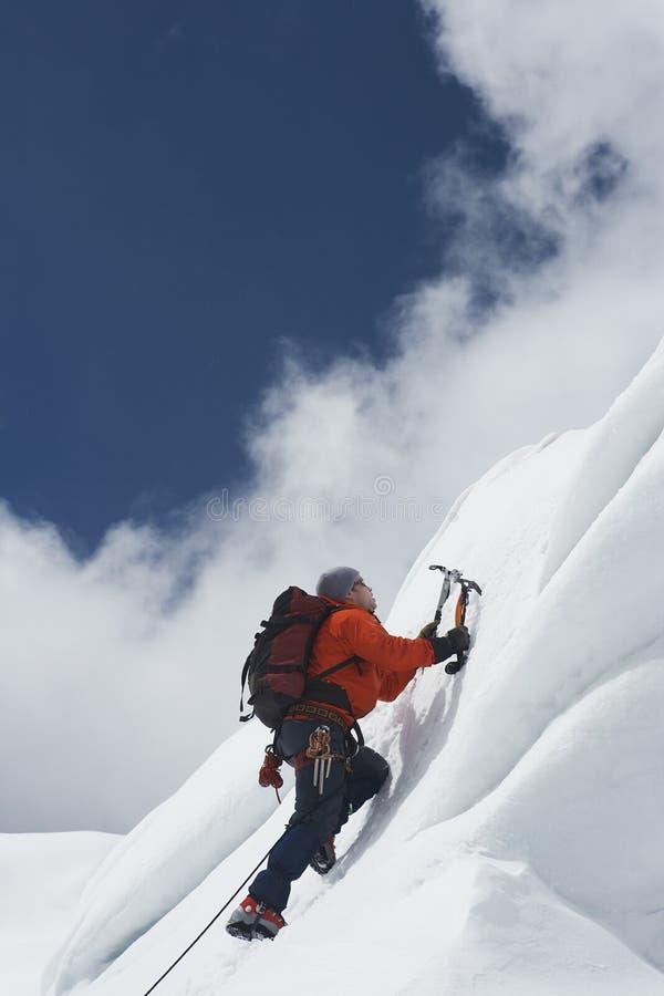 Snöig lutning för bergsbestigare gå upp med yxor royaltyfri bild