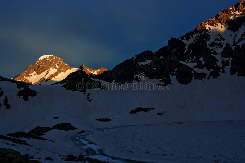 Snöig maximum för berg som är upplyst vid inställningssolen royaltyfri bild