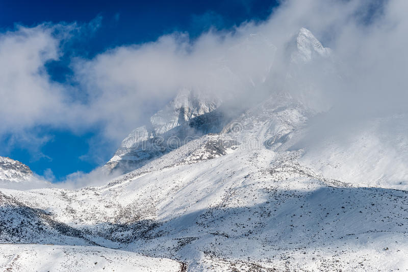 Snöig maximum som döljas av moln arkivfoto