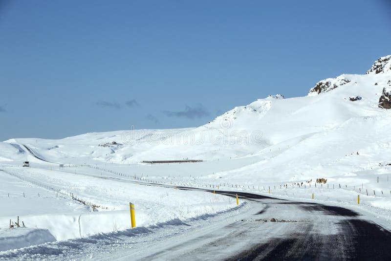 Snöig och hal väg med vulkaniska berg i vintertid royaltyfri fotografi