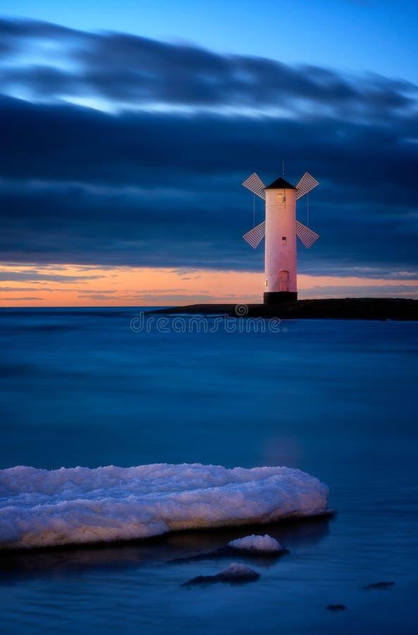 Snöig plats för baltiskt hav Härlig solnedgång över väderkvarn-formad arkivbild
