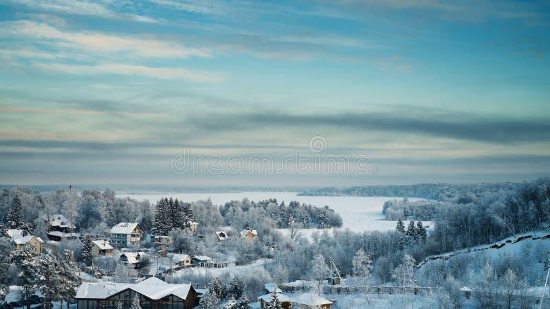 Snöig skog och stugor och med is sjö på solnedgången fotografering för bildbyråer