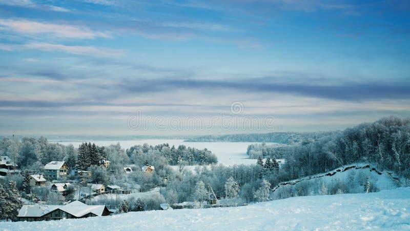 Snöig skog och stugor och med is sjö på solnedgången royaltyfri bild