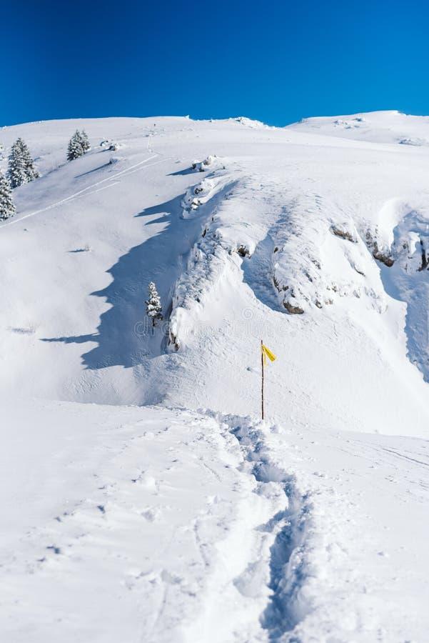 Snöig slinga upptill av berget med vägvisare och klar blå himmel arkivfoto