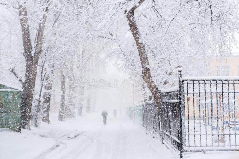 Snöig stadsväg mellan träd och knappt synligt gå folk under rikligt snöfall royaltyfri foto