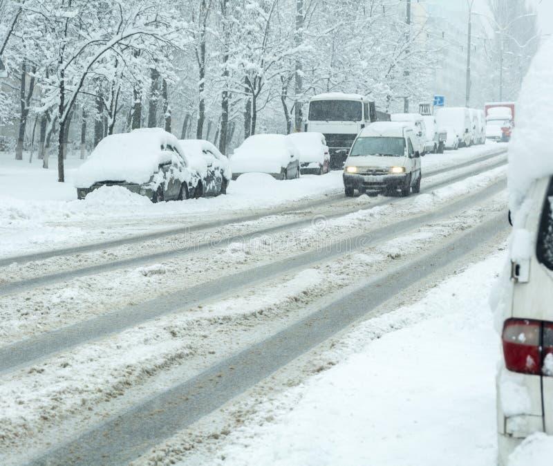 Snöig vinterväg med bilar i snöstorm royaltyfri bild