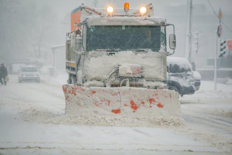Snöplog på gator under tungt snöfall royaltyfri foto