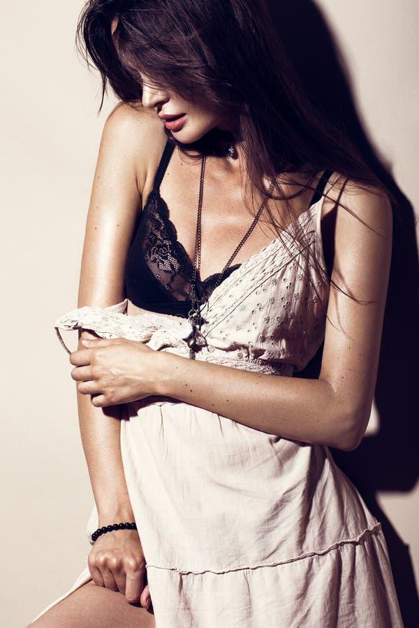 Snör åt den sexiga kvinnan för glamourmode med brunbränd hud, löst hår, aftonsminket i en sommarklänning och svart underkläderna arkivbilder