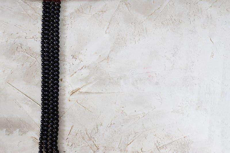 Snör åt den svarta pärlan för bijouterie tre som vertikal libe på grå texturerad cementyttersida som är horisontal med kopierings royaltyfri bild