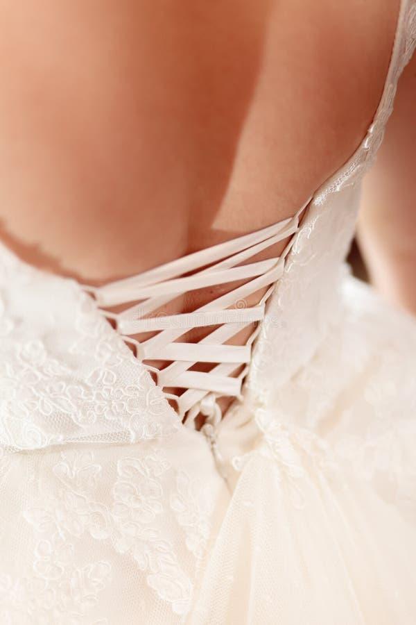 Snöra åt bröllopsklänningen royaltyfri bild