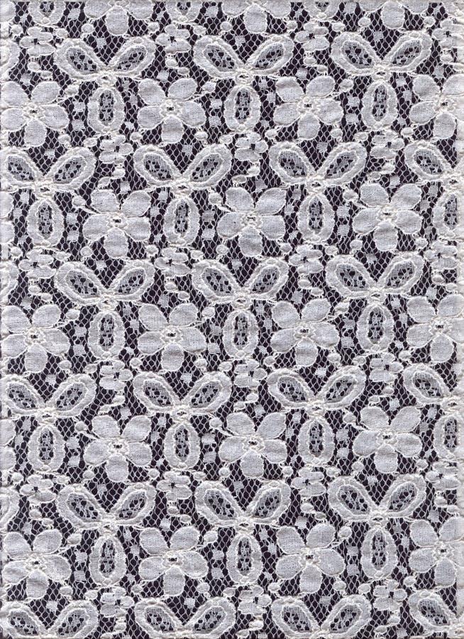 Snöra åt på en svart bakgrund bakgrundsblack snör åt white lacy bakgrund arkivfoto