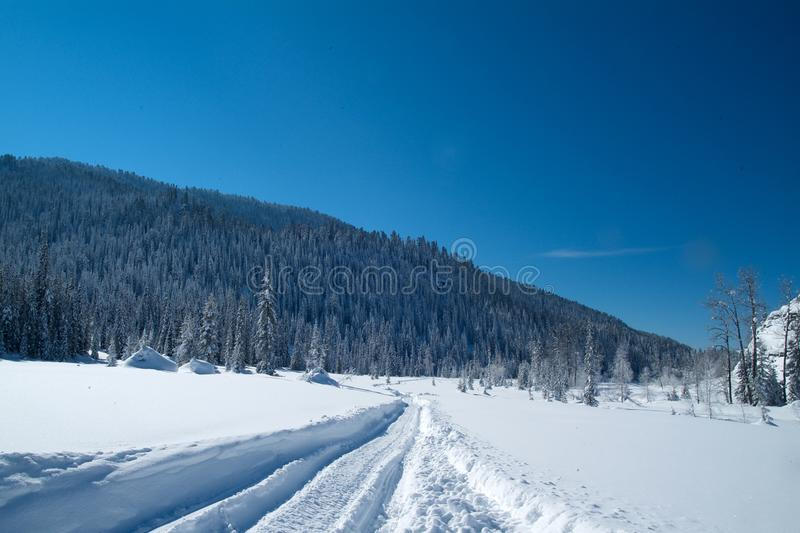 Snövesslaspårfläck på snön mot berg och en blå himmel royaltyfria foton