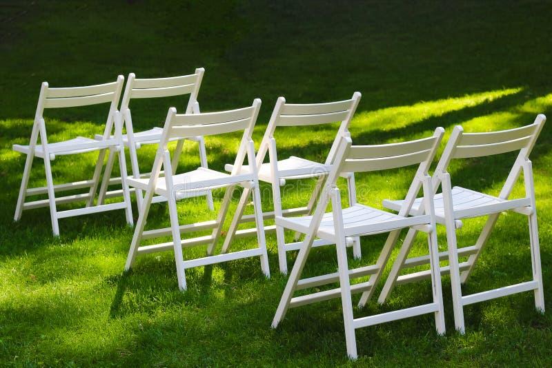 Snövita trästolar för gäster på en utomhus- gifta sig ceremoni arkivbild