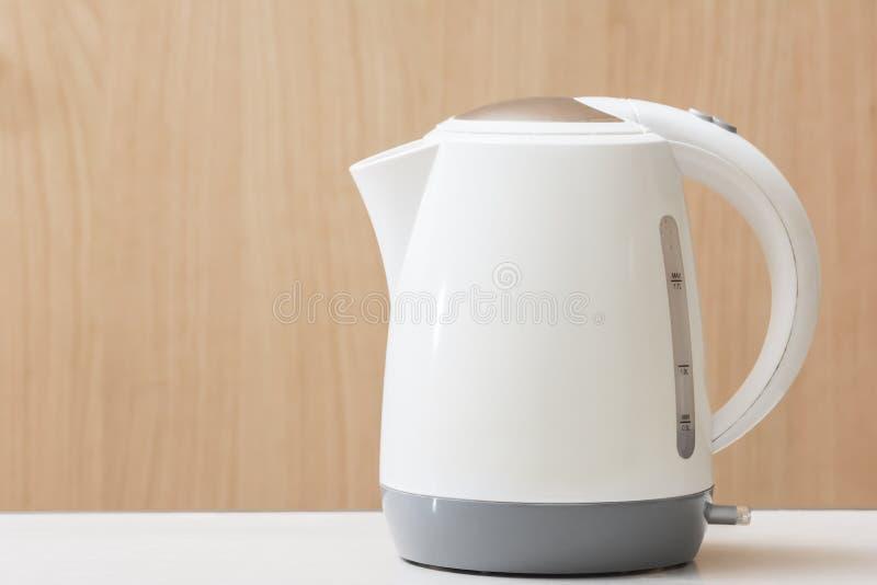 Snabb böld för vit elektrisk kokkärl på tabellen och träbakgrund royaltyfria foton
