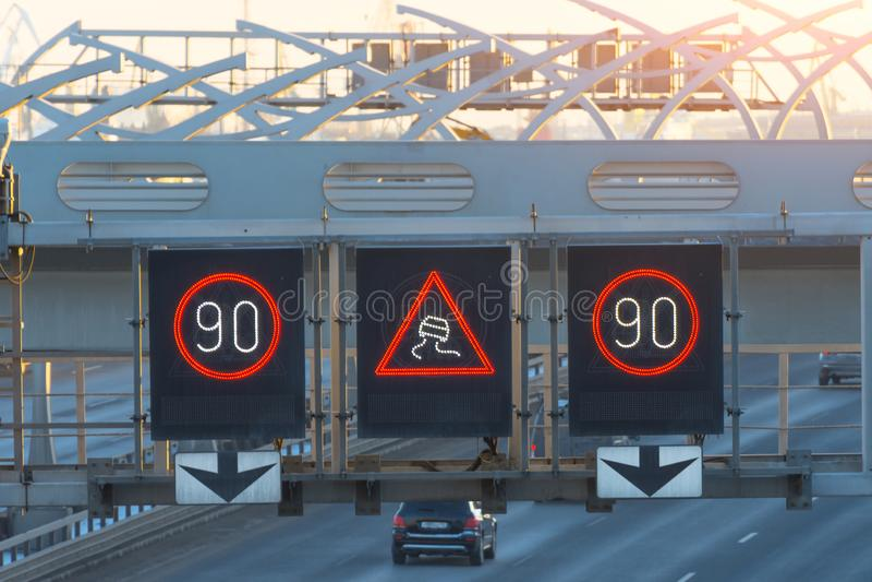 Snabb huvudväg med trafikbilar och elektroniskt växelverkande hastighetsbegränsningtecken och en hal vägvarning royaltyfria bilder