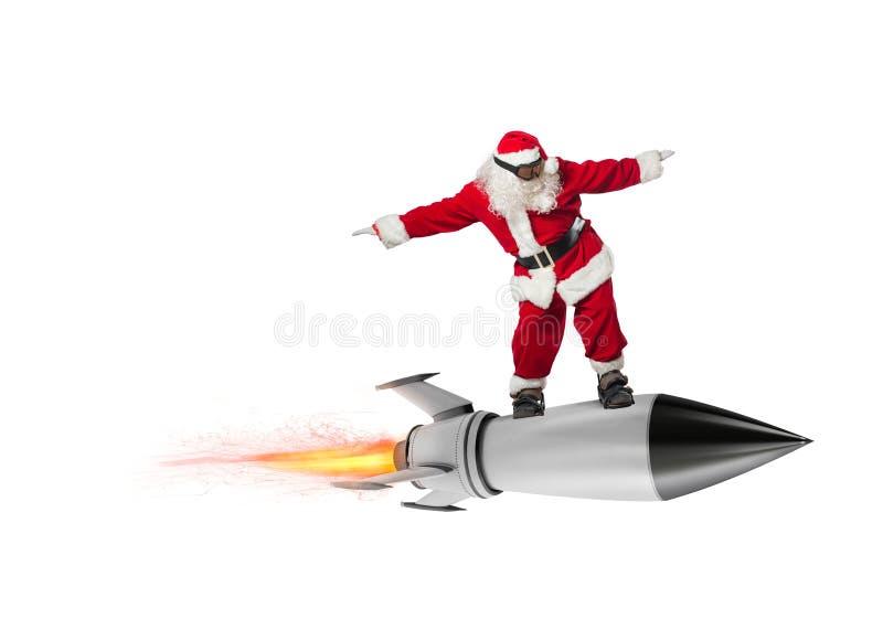 Snabb leverans av julgåvor Santa Claus som är klar att flyga med en raket som isoleras på vit bakgrund royaltyfria foton
