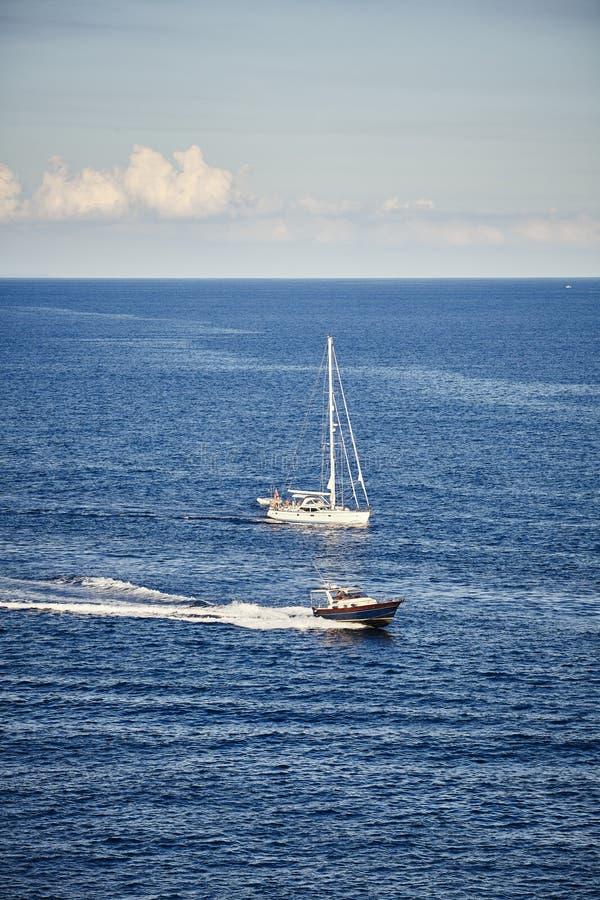Snabb motorbåt och segelbåt vid havet arkivbilder