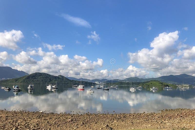 Snabb motorbåt, segelbåt, yacht, sjö och blå himmel med reflexionsskugga arkivfoto