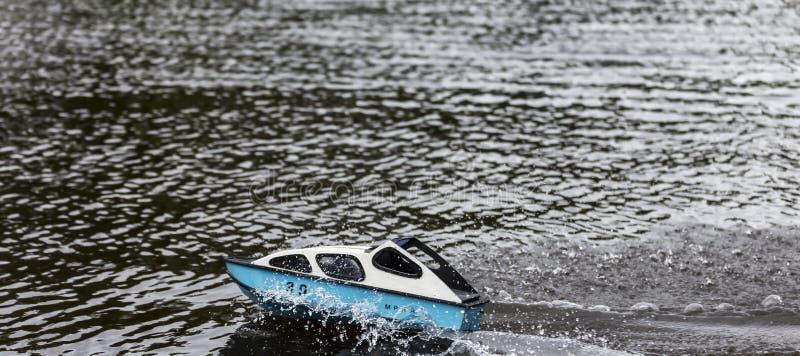Snabb motorbåt som springer på en sjö orsaka vågor royaltyfri bild