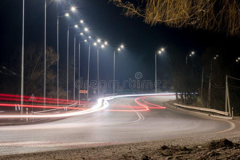 snabb moving natttrafik timmar liggandes?songvinter begrepp av v?gen, sn?- och isborttagningen, faran och s?kerheten av r?relse,  royaltyfri bild