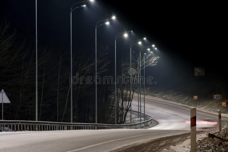 snabb moving natttrafik timmar liggandes?songvinter begrepp av v?gen, sn?- och isborttagningen, faran och s?kerheten av r?relse,  arkivfoto