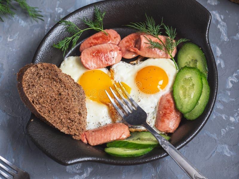 Snabb och hurtig frukost av f?rvanskade ?gg och korvar p? en svart platta, en gurka, skivade skivor, ett stycke av svart br?d och royaltyfria foton
