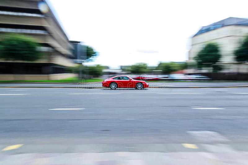 Snabb röd flyttning för sportbil och att panorera royaltyfri bild