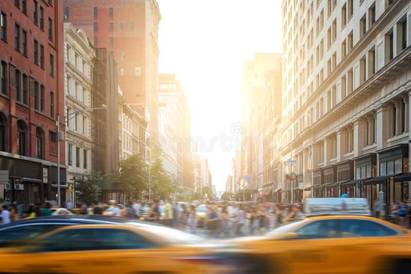 Snabb-stegat liv i New York City gataplats med taxiar som kör ner den 5th avenyn och folkmassor av folk i New York City royaltyfri foto