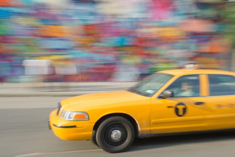 Snabb taxi på gatan med färgväggen royaltyfria foton