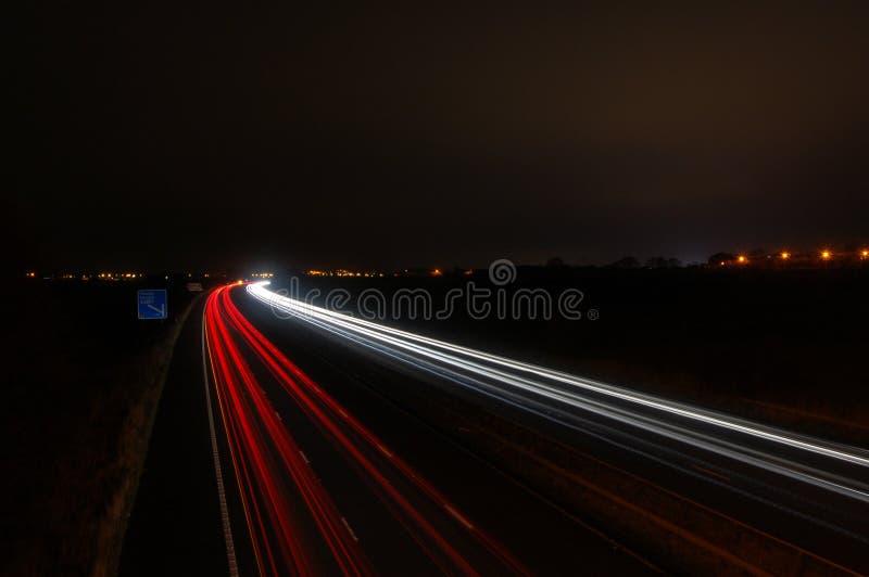 Snabba rörande motoriska bilar på motorwayen på natten arkivfoton