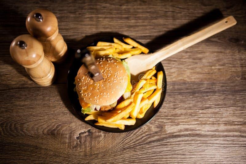 Snabbmat av smakliga läckra hamburgare på träbakgrund nästa t arkivbild