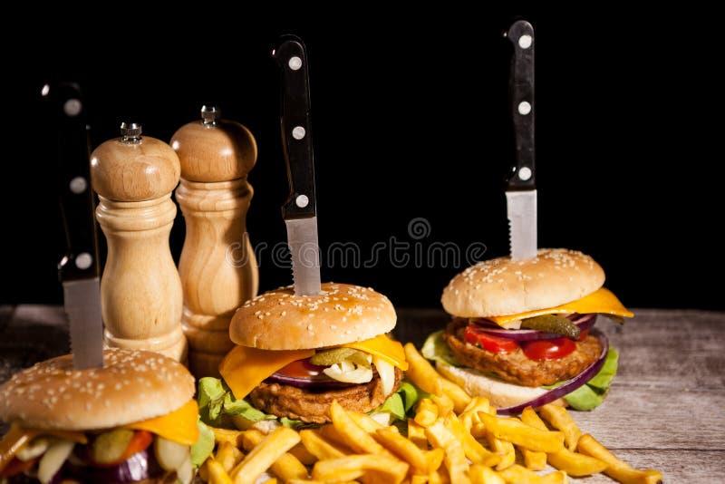 Snabbmat av smakliga läckra hamburgare på träbakgrund nästa t royaltyfria bilder