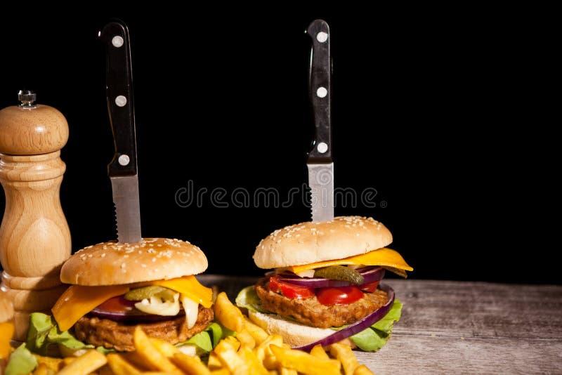 Snabbmat av smakliga läckra hamburgare på träbakgrund nästa t arkivfoto