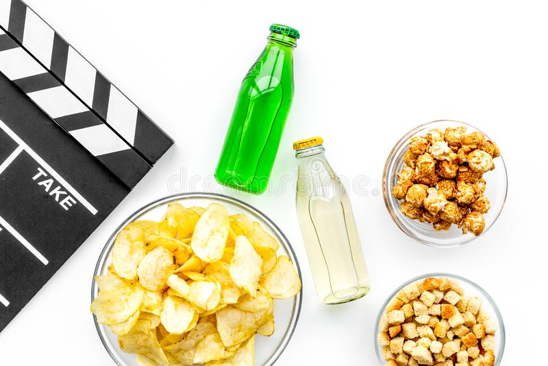 Snabbmat för hållande ögonen på film Chips popcorn, skorpor, drinkar nära clapperboard på bästa sikt för vit bakgrund royaltyfri foto