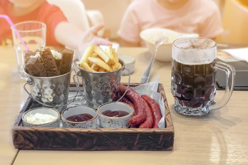 Snabbmat i pommes frites för kaférestaurangmellanmål, olika typer för ölmörker av såser och kortkortkorvar arkivfoto