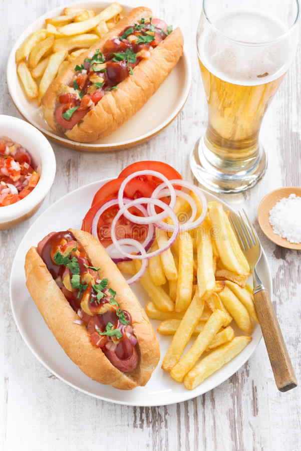 Snabbmat - varmkorv med pommes frites, öl och mellanmål arkivfoton