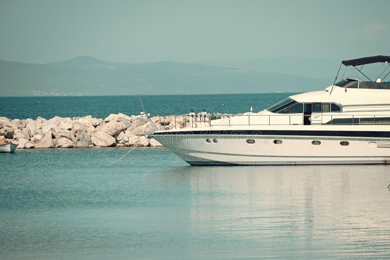 Snabbt fartyg, lyxig yacht i skeppsdocka i havet, blå himmel på bakgrund Den vita lyxiga yachten, marin- glidljud på havet ytbeha royaltyfri fotografi