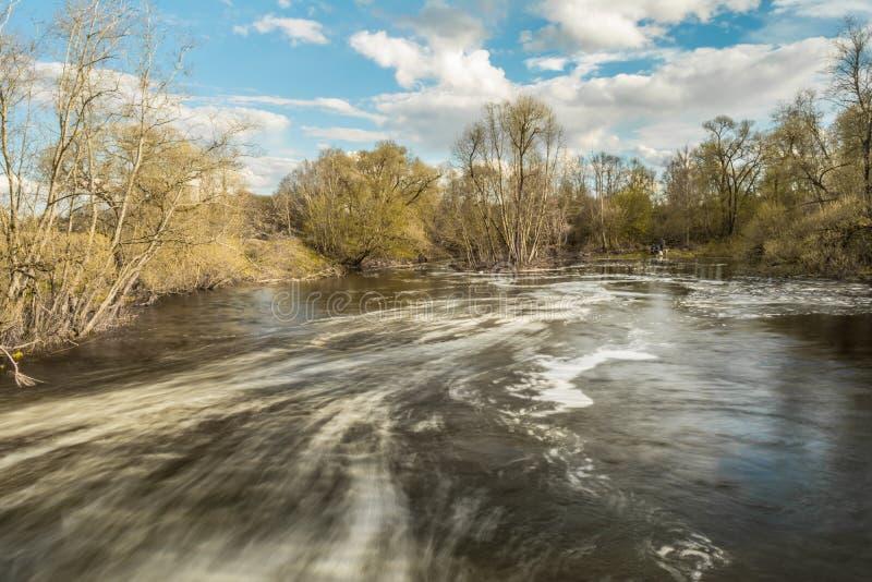 Snabbt flöde av flodpasserandeen nära träd och buskar, kallt vattennedgångar över de förstörda konkreta platinastrukturerna arkivbilder