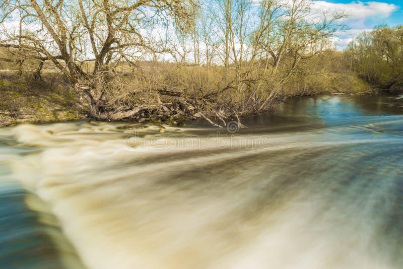 Snabbt flöde av flodpasserandeen nära träd och buskar, kallt vattennedgångar över de förstörda konkreta platinastrukturerna arkivfoto