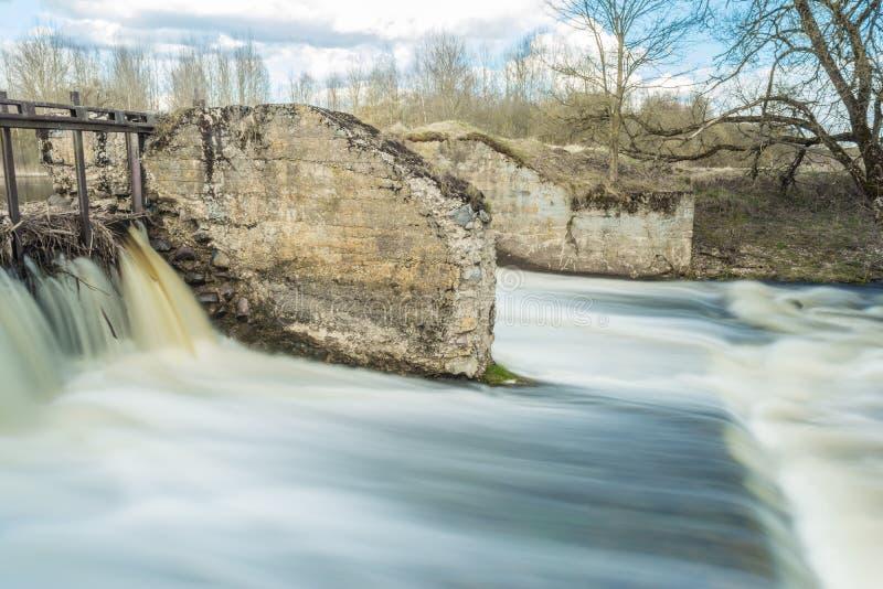 Snabbt flöde av flodpasserandeen nära träd och buskar, kallt vattennedgångar över de förstörda konkreta platinastrukturerna arkivbild