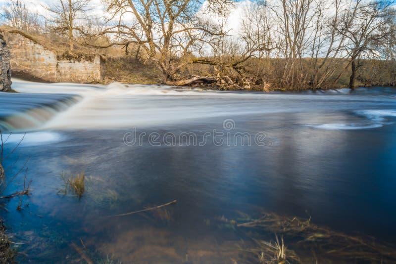 Snabbt flöde av flodpasserandeen nära träd och buskar, kallt vattennedgångar över de förstörda konkreta platinastrukturerna royaltyfri foto