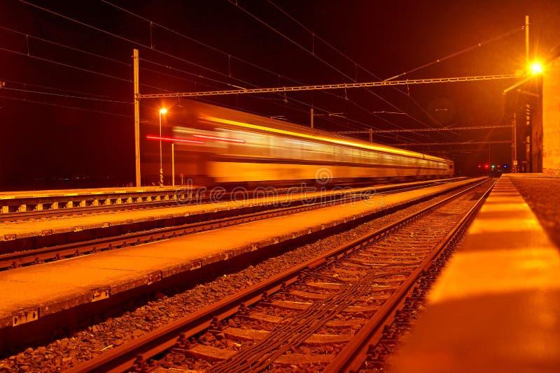 Snabbt passageraredrev på spår med effekt för rörelsesuddighet på natten Järnvägsstation i Tjeckien royaltyfri bild