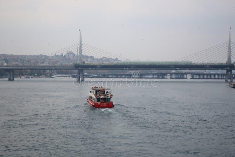 Snabbt rött fartyg som svävar till den guld- horn- tunnelbanabron royaltyfria foton