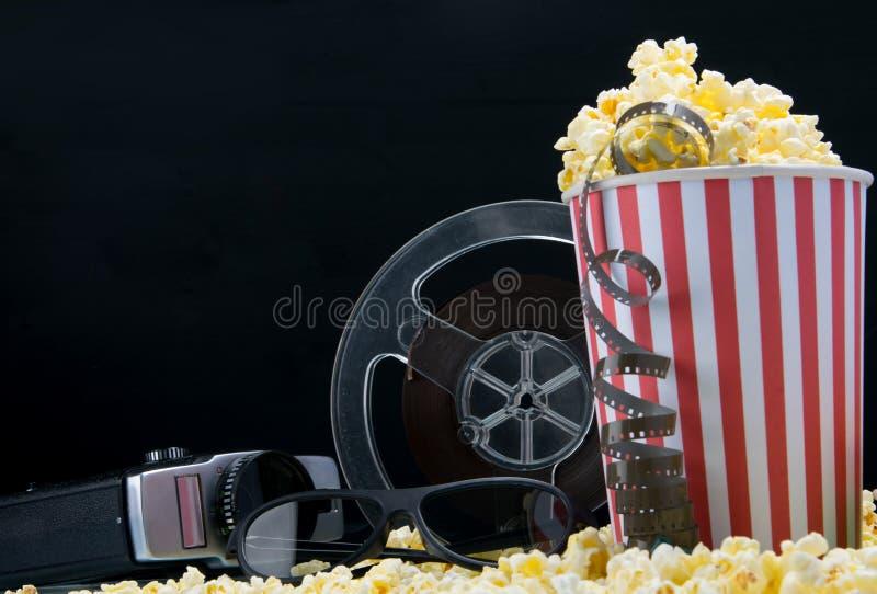 snack bar del cine en fondo negro, cubo de nachos con la cinta video y cámara retra fotos de archivo