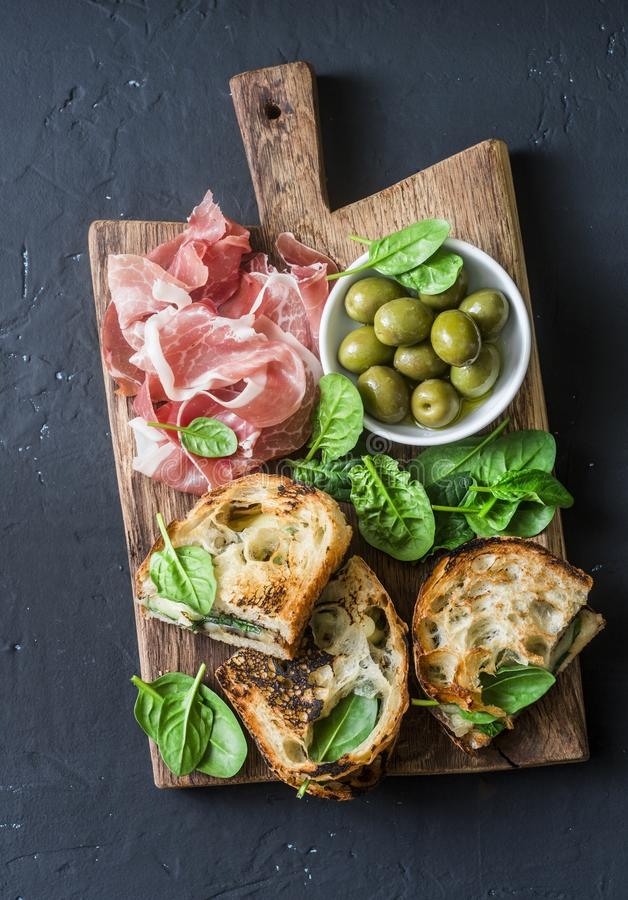 Snack board - prosciutto, olives, grilled mozzarella spinach sandwiches on dark background, top view. Mediterranean style snack, a royalty free stock photography