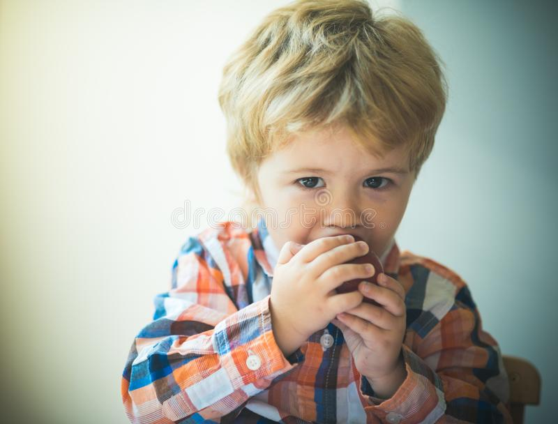 Snack. Boy eating apple. Child eating fruit. Red apple biting. Little kid boy portrait, eating red apple. Healthy food royalty free stock photography
